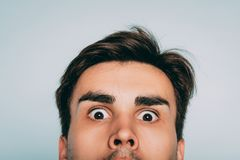 Startle crazy eccentric whimsical man face peek. Startled crazy eccentric whimsical man face closeup. portrait of a young brunet guy on light background peek out stock images