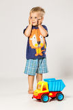 Startled Boy playing with the big plastic car. Light colours Stock Photos