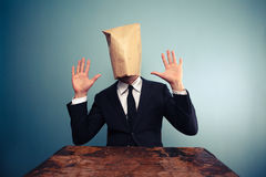 Startled businessman with bag over head raising his hands Royalty Free Stock Image