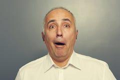 Startled senior man over dark Royalty Free Stock Images