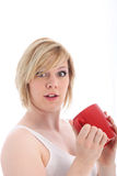 Startled woman holding a mug of coffee Royalty Free Stock Photography