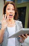 Startled Woman with Tablet Computer Stock Image