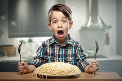 Startled yound boy with noodles stock photography