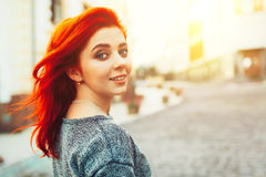 Startled young redhead woman looking back over her shoulder at the camera as she strolls down a deserted urban street Royalty Free Stock Photos