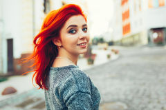 Startled young redhead woman looking back over her shoulder at the camera as she strolls down a deserted urban street Royalty Free Stock Photography