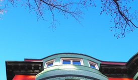 Brightly Colored Scene of Sky, Tree Buds, and Brightly Painted Architecture. A startlingly bright scene of robin blue sky, buds on branches overhead, and a stock photography