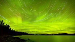 Startrails在湖Laberge的北极光展示 免版税库存照片