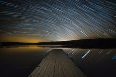 Startrails über dem See Stockfotografie