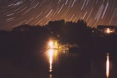 Startrails da noite na casa do lago Imagem de Stock
