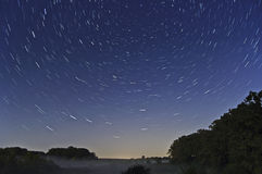Startrails and Fog. This shows the stars apparent motion after 10 minutes over a foggy pond Royalty Free Stock Photos
