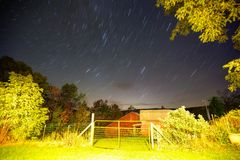 Startrails over a barn with gate Royalty Free Stock Photo
