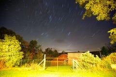 Startrails sobre un granero con la puerta Foto de archivo libre de regalías