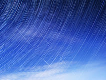Startrails star lights the night sky plane satellite space universe earth clouds. Photos of stars on long exposure Stock Photos