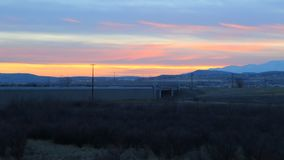 From wide to zoom view of a sunset with evening traffic and mountains in the background stock footage