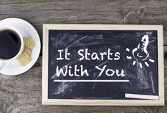 It Starts With You. Chalk board on a wooden table. It Starts With You. Chalk board on a wooden table royalty free stock photography
