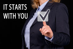 It starts with you. Text 'it starts with you' message in white uppercase letters on the touch screen of a computer with a businesswoman in dark suit and shirt Royalty Free Stock Images