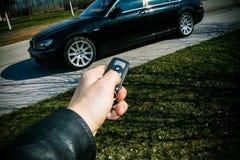 Starttangent av BMW 750 i en manlig hand Arkivbild
