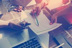 Startteambrainstorming Vermarktungsplanuntersuchung Schreibarbeit und Handy stockfotos