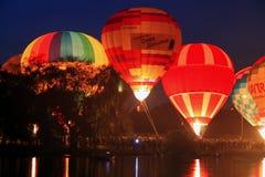 Startung dos baloons do ar quente a voar no céu da noite Imagem de Stock