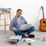 Startup бюджет деятельности предпринимателя с компьтер-книжкой на домашнем офисе Стоковые Фото