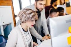 Startup симпатичные деловые партнеры работая совместно в офисе просторной квартиры Стоковые Изображения
