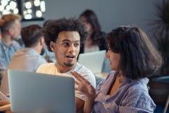Startup affär och nytt mobilt teknologibegrepp med unga multietniska par i modern ljus kontorsinre arkivbild