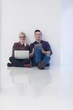 Startup affär, par som arbetar på bärbar datordatoren på kontoret Fotografering för Bildbyråer