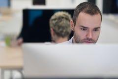 Startup affär, programvarubärare som arbetar på den skrivbords- datoren Royaltyfria Bilder