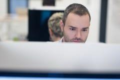 Startup affär, programvarubärare som arbetar på den skrivbords- datoren arkivbilder