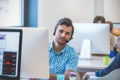 Startup affär, programvarubärare som arbetar på den skrivbords- datoren Arkivbild