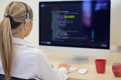 Startup affär, ung kvinna som programvarubärare som arbetar på datoren på det moderna kontoret arkivbild