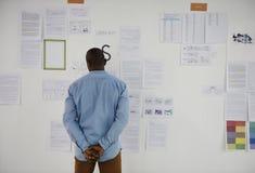 Startup affärsfolk som ser på Th för information om strategibräde Arkivfoto