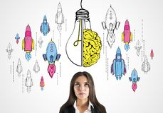 Startup, brainstorm and idea concept. Thoughtful young businesswoman with creative lamp, brain and rocket sketch on light background. Startup, brainstorm and stock image