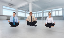Startup business. Young business people meditating in empty office space royalty free stock photos