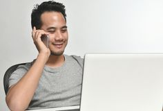 Startup business man smiling while talking on the phone and having fun at work. Casually-dressed startup business man smiling while talking on the phone and Royalty Free Stock Images