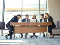Startup business team on meeting in modern bright office interior and working on laptop. Stock Photography
