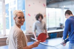 Startup business team playing ping pong tennis. Group of young startup business people playing ping pong tennis at modern creative office Royalty Free Stock Images