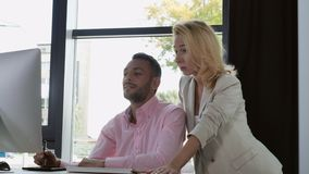 Startup company develops design. Two designers working in modern office. Adult caucasian businesswoman standing near handsome mixed race worker. People looking stock footage