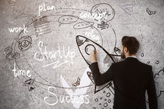 Startup concept. Attractive young man drawing rocket sketch on concrete wall. Startup concept royalty free stock photo