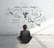 Startup concept with business sketch. Startup concept with businessman sitting on concrete floor and looking at sketch drawn on white brick wall Stock Image