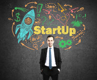 Startup concept with colorful sketch. Startup concept with confident young businessman and colorful rocket ship sketch on concrete background Stock Image