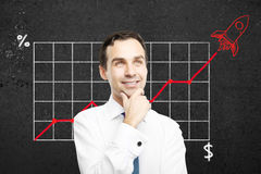 Startup concept with happy businessman. Start up concept with happy thoughtful businessman. Business chart with red rocket ship on concrete wall in the Stock Photography