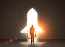 Startup concept rocket gap. Start up concept with businessman holding briefcase and standing in front of rocket shaped gap in wall, revealing sunlit New York stock photography