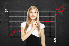 Startup concept with thoughtful businesswoman. Start up concept with pretty thoughtful businesswoman. Business chart with red rocket ship on concrete wall in the Stock Images