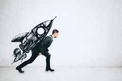 Startup and effort concept. Young businessman carrying creative rocket sketch on his back on concrete wall background. Startup and effort concept royalty free stock photography