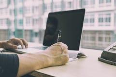 startup man som använder på en bärbar dator som skriver anmärkningen, medan sitta woen Royaltyfri Bild