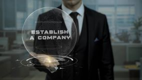 Startup management tutor presents concept Establish a Company using hologram. Entrepreneur in suit holds animated virtual Earth on his hand, when talks about stock video