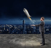 Startup of a new company. Concept of new business. Businessman throws a rocket in the sky. Startup of a new company concept Royalty Free Stock Photo