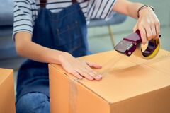Startup small business concept, young Asian woman owner working and packing on the box to customer at the sofa in home office.
