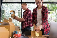 Startup small business owner working with computer at workplace. Freelance men & women seller check product order, packing goods for delivery to customer Stock Image
